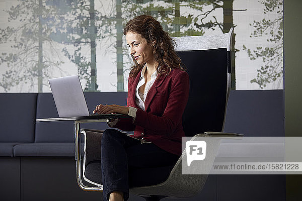 Businesswoman sitting in armchair in office using laptop