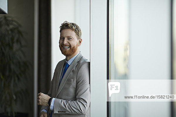 Portrait of a happy businessman at the window