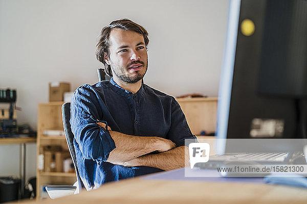 Porträt eines am Schreibtisch sitzenden Geschäftsmannes in einem hölzernen Großraumbüro