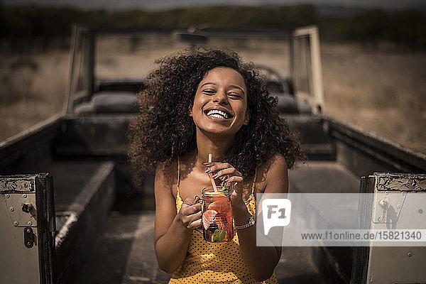 Porträt einer lachenden Frau  die im Safari-Bus frischen Eistee trinkt
