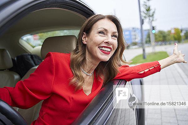 Porträt einer glücklichen reifen Frau  die sich aus dem Autofenster lehnt