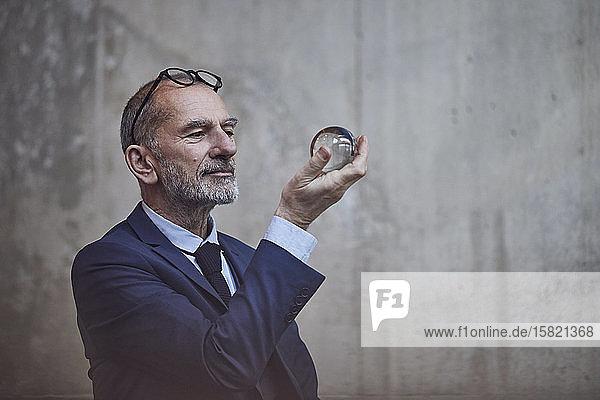 Leitender Geschäftsmann schaut in die Kristallkugel