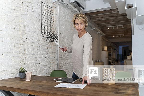 Reife Frau arbeitet am Schreibtisch im Architekturbüro