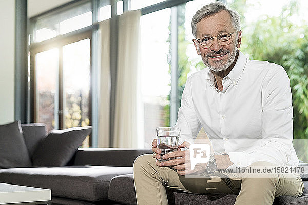 Portrait of smiling senior man in modern design living room sitting on couch holding glass of water