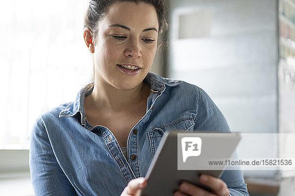 Porträt einer lächelnden Frau mit Tablette