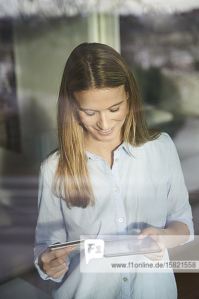 Smiling blond young woman using tablet and credit card