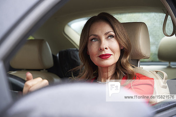 Portrait of pensive mature woman in car