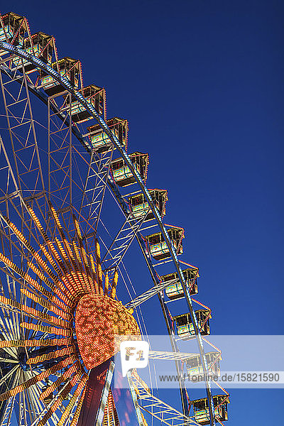 Deutschland  Bayern  München  Niederwinkelansicht des Riesenrads  das in der Abenddämmerung gegen den klaren Himmel leuchtet