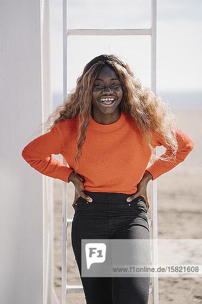 Porträt einer lachenden Teenagerin am Strand