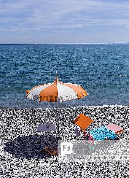 Frankreich  Alpes-Maritimes  Cagnes-sur-Mer  Sonnenschirm und Liegestuhl am felsigen Küstenstrand mit klarer Horizontlinie über dem Mittelmeer im Hintergrund