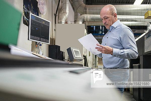 Geschäftsmann hält Papier an einer Maschine in einer Fabrik