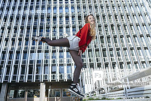 Glückliche junge Frau balanciert auf Rollschuhen in der Stadt