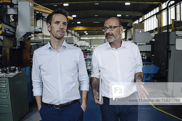 Zwei Männer unterhalten sich in einer Fabrik