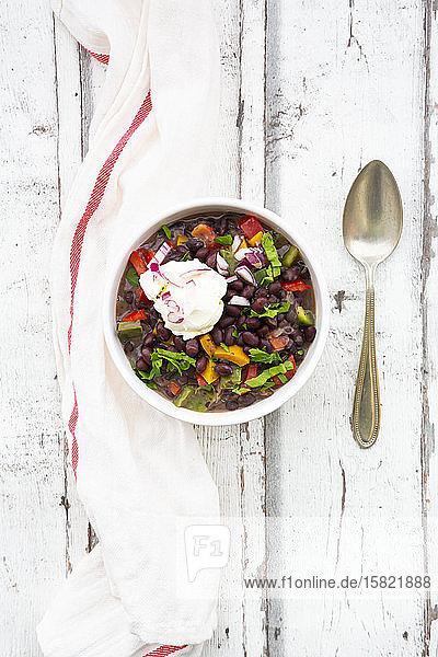 Schüssel schwarze Bohnensuppe mit Paprika  Koriander  Sauerrahm und roten Zwiebeln