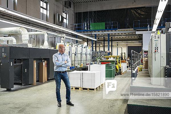 Geschäftsmann  der in einer Fabrik steht und sich umsieht