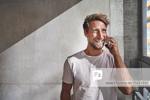 Happy young man wearing t-shirt talking on the phone