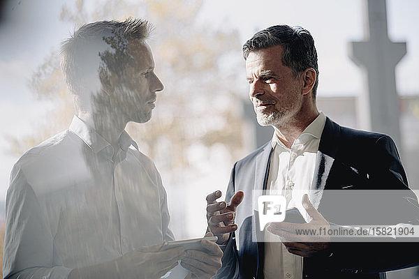Zwei Geschäftsleute im Gespräch am Fenster