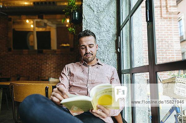 Mann liest Buch in einem Cafe am Fenster
