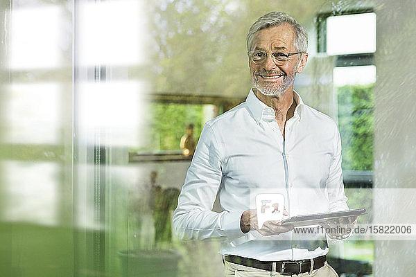 Lächelnder älterer Mann mit grauen Haaren in modernem Design Wohnzimmer hält Tablette