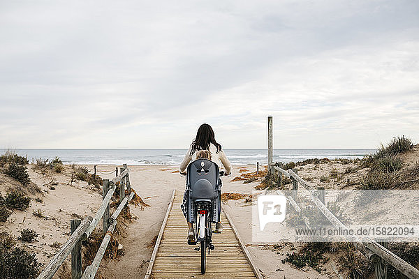 Woman riding bicycle on a boardwalk in the dunes with daughter in child's seat