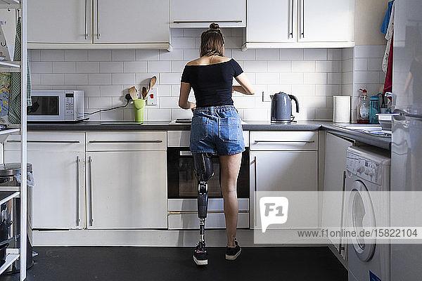 Rückansicht einer jungen Frau mit Beinprothese in der häuslichen Küche