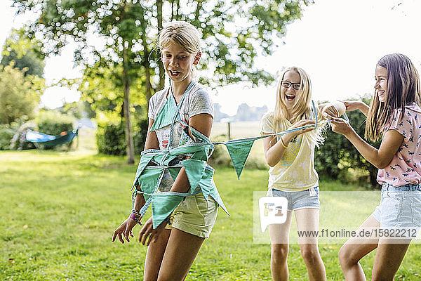Glückliche Mädchen amüsieren sich auf einer Geburtstagsfeier im Freien Glückliche Mädchen amüsieren sich auf einer Geburtstagsfeier im Freien