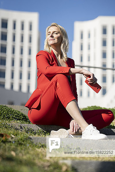 Blond businesswoman wearing red suit and sitting on stairs