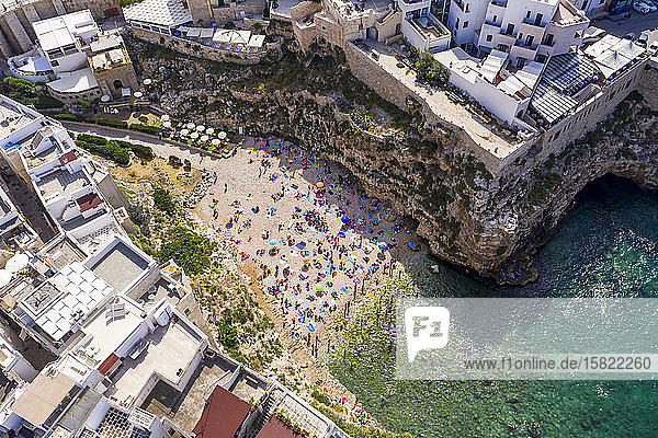 Italy  Polignano a Mare  Aerial view of crowd of people relaxing on sandy beach of coastal town in summer