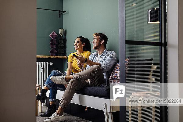 Glückliches junges Paar sitzt zu Hause auf der Couch und sieht fern Glückliches junges Paar sitzt zu Hause auf der Couch und sieht fern