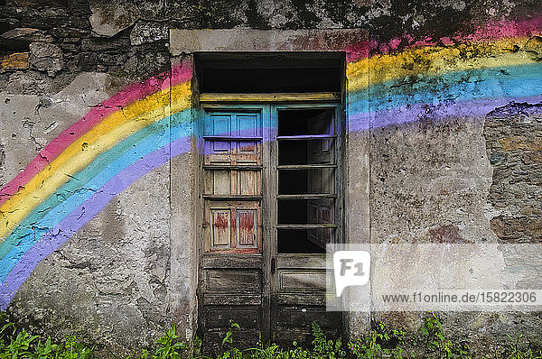 Spain  Province of A Coruna  San Saturnino  Rainbow painted across doors of abandoned house