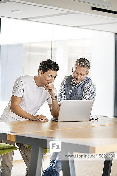 Ein älterer Geschäftsmann arbeitet mit einem jungen Kollegen zusammen und benutzt einen Laptop