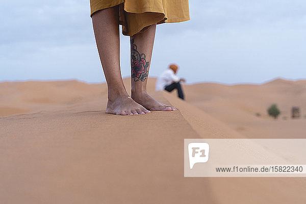 Füße einer auf einer Sanddüne in der Sahara stehenden Frau  Merzouga  Marokko