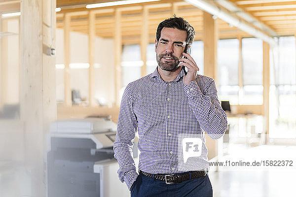 Geschäftsmann am Telefon im hölzernen Großraumbüro