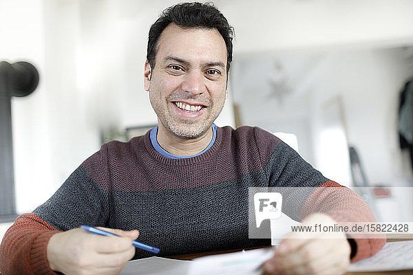 Porträt eines lächelnden reifen Mannes mit Dokumenten  der zu Hause am Tisch sitzt