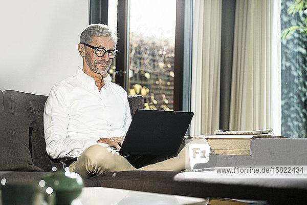 Älterer Mann mit grauen Haaren in modernem Design-Wohnzimmer  der im Heimbüro am Laptop arbeitet