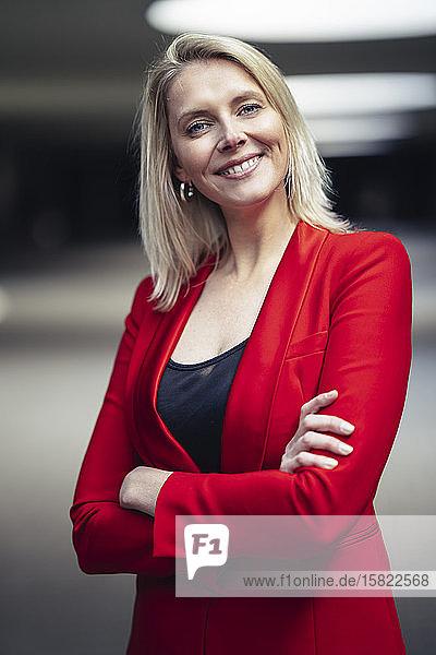 Blonde lächelnde Geschäftsfrau mit verschränkten Armen  die einen roten Anzug trägt und in die Kamera schaut