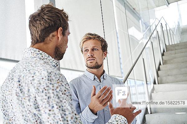 Zwei junge Geschäftsleute unterhalten sich im Treppenhaus