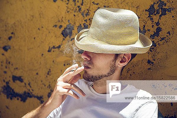 Junger Mann sitzt vor der abblätternden gelben Wand und raucht eine Zigarette