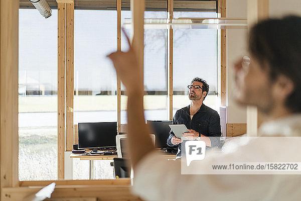 Geschäftsmann mit Tablett im hölzernen Großraumbüro