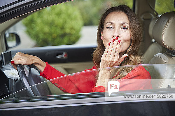 Portrait of smiling mature woman in car blowing a kiss