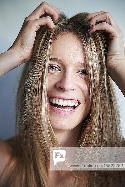 Porträt einer lachenden blonden jungen Frau mit Händen im Haar