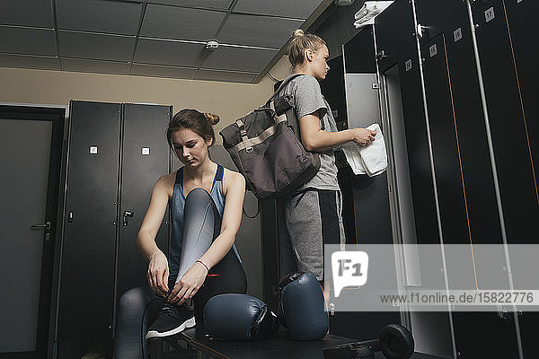 Two young women in locker room of a boxing club