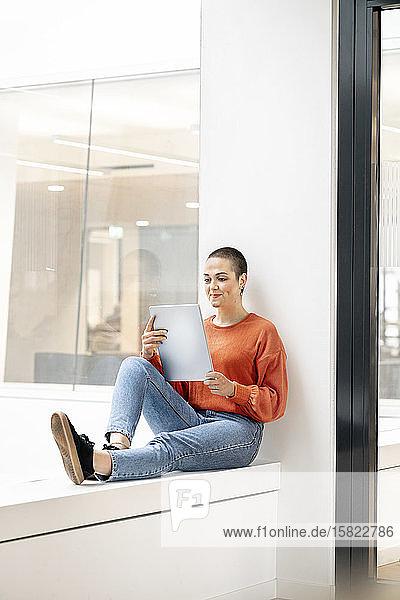 Entspannte Geschäftsfrau sitzt auf der Fensterbank eines Bürogebäudes und benutzt ein digitales Tablet
