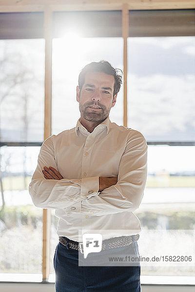 Porträt eines selbstbewussten Geschäftsmannes am Fenster im Großraumbüro