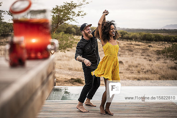 Happy couple dancing on deck of a lodge  Cape Town  South Africa