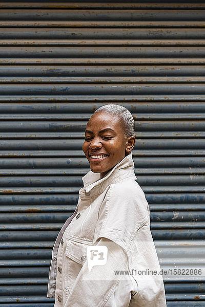 Porträt einer glücklichen Frau an einem Rollladen