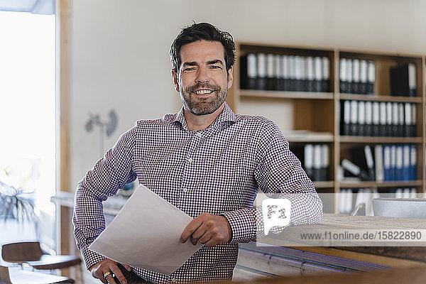 Porträt eines lächelnden Geschäftsmannes mit Dokument im hölzernen Großraumbüro