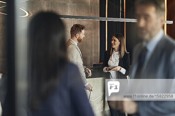 Business people talking at reception in hotel lobby