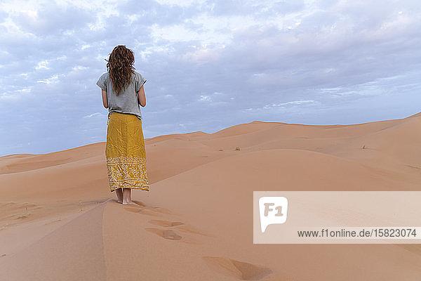 Junge Frau auf einer Sanddüne in der Wüste Sahara  Merzouga  Marokko