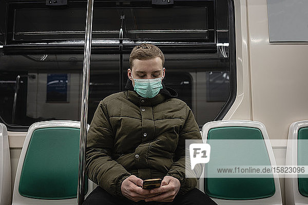 Young man in commuter train  wearing face mask  using smartphone